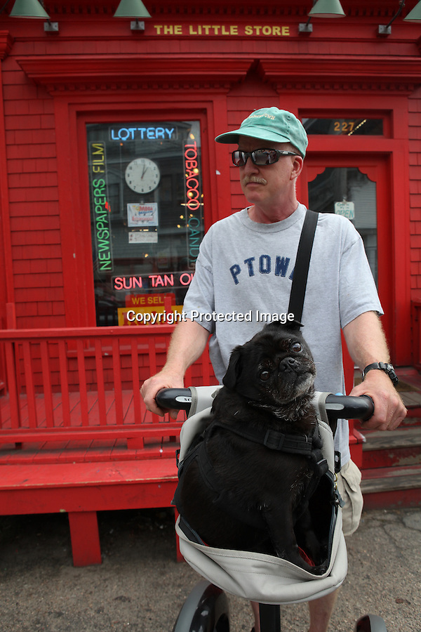 "Provincetown artist, Chip Brock is photographed with his pug, Chu Chi, in front of the well-known ""Little Red Store"" on Commercial St. in Provincetown, MA.  The store is just one of the many Chip and Chu Chi visit on Chip's Segway to say hi to Chu Chi's ""friends"" and receive dog biscuits.   Provincetown was recently voted most dog-friendly town in the U.S.A.  by Dog Fancy Magazine. 8/6/10 Julia Cumes"