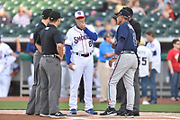Umpires Alex MacKay, Cody Clark and Edwin Moscoso meet with Tennessee Smokies manager Mark Johnson (8) and Mississippi Braves manager Luis Salazar (4) before a game at Smokies Stadium on April 12, 2017 in Kodak, Tennessee. The Braves defeated the Smokies 6-2. (Tony Farlow/Four Seam Images)