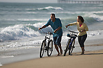 Mature couple walking with bicycles at seashore, smiling