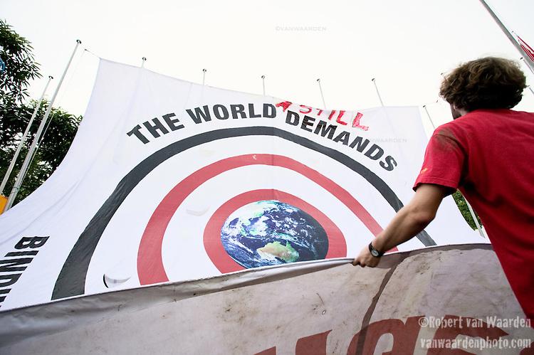 International Youth unfurl a massive banner demanding binding targets during the last day of the UN Climate Negotiations in Bali. (©Robert vanWaarden Nusa Dua, Indonesia, Dec. 14, 2007)