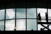 Crews work on windows in the main terminal of Lambert- St. Louis International Airport on April 23, 2011 after storms last night damaged both the interior and exterior of the airport. The airport was closed all day today and officials hope to reopen tomorrow. REUTERS/Sarah Conard (UNITED STATES)