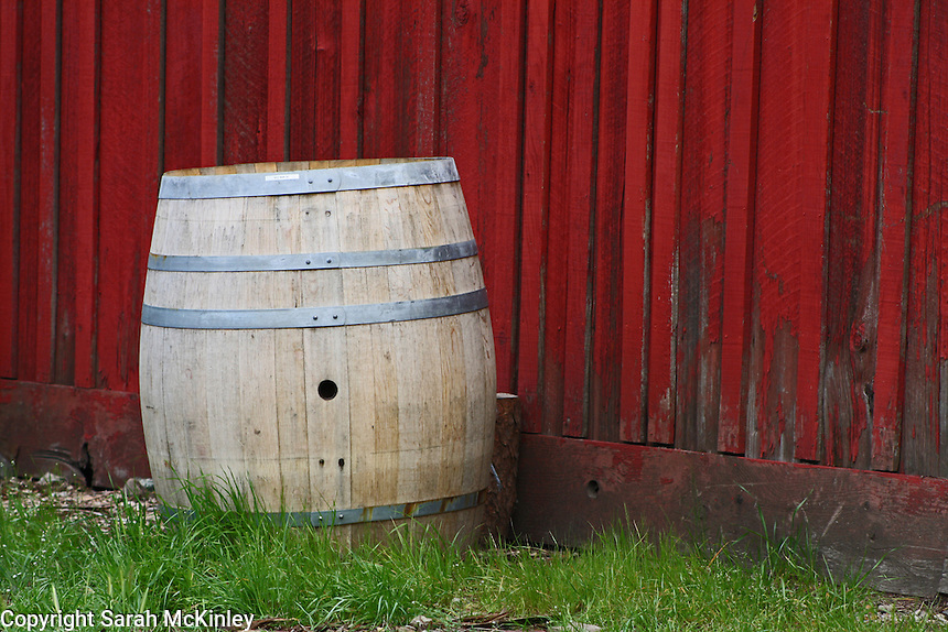 A barrel stands next to a red, wood barn near Calistoga in Napa County in Northern California.