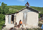 As Meisier Genise sits in the doorway with her two childen, Deravil Samile roofs her house in Picmy, a village on the Haitian island of La Gonave, one of many houses built by Service Chrétien d'Haïti for survivors of the 2016 Hurricane Matthew. SCH is a member of the ACT Alliance.
