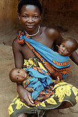 Kisamba, Tanzania. Mother with twin babies, one slung round her, the other on her knee; Lake Tanganyika.