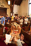 The Sunday service led by Reverend Matthew Nelson at Inman Park United Methodist Church in Atlanta, Georgia August 5, 2012...Mary Sage reads through a hymnal with her son Silver Sage, 3.