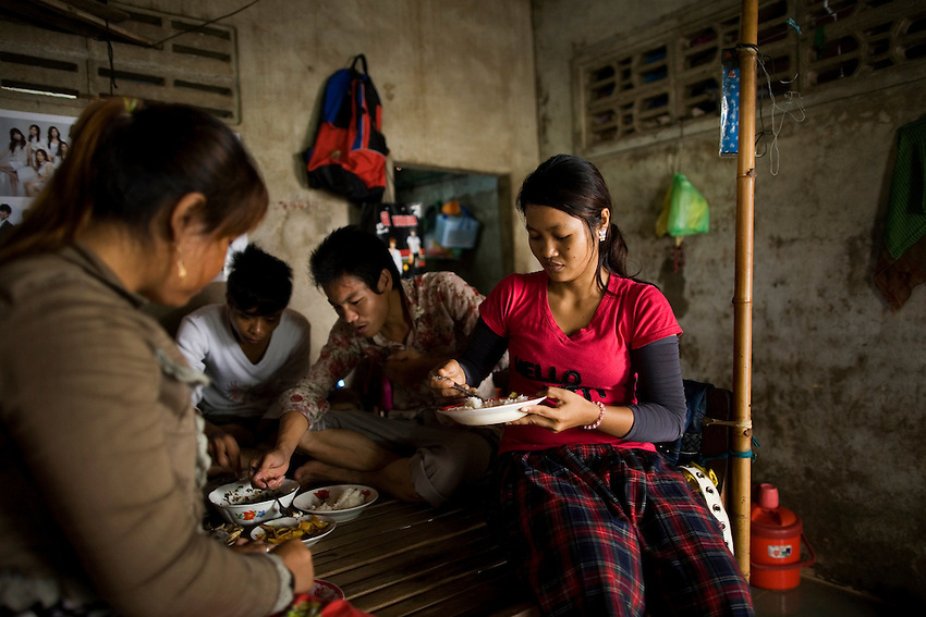 Garment factory workers employed by PCCS Garments Ltd, a manufacturer of Adidas apparel, have lunch at home in between shifts in Phnom Penh, Cambodia, September 16, 2010.