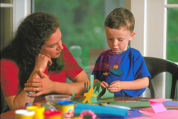 woman watching young boy working with crafts at table