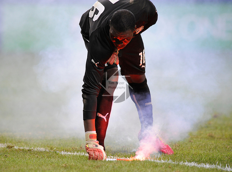 Soccer - International Friendly - Bosnia- Ivory Coast.<br /> Ivory Coast goalkeeper Sylvain Gbouhouo (16) picks up a road flare that puts a red glow on his face. The flare was hurled onto the field near the end of the game. Several flares and other smoke producing devices were thrown to the field as the game came to an end, with Bosnia winning, 2-1. Bosnia played Ivory Coast in an international friendly game during &quot;The Road To Brazil&quot; series. The game was played at the Edward Jones Dome in St. Louis, Missouri on Friday May 30, 2014.