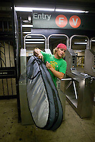 A surfer carries his surfboard through the turnstyles at the Lower East Side 2 Av subway station in New York, United States, after a morning surf at Far Rockaway beach, 17 September 2005. Photo Credit: David Brabyn.