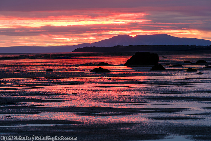 Sunset over Mt. Susitna -- aka: Sleeping Lady -- and mudflats of Turnagain Arm with rocks at low tide.  Summer   Anchorage, Alaska <br />