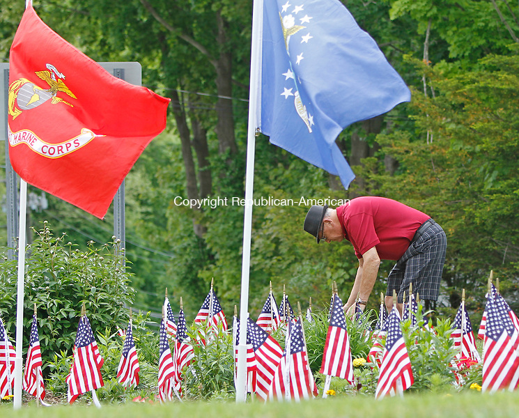 Harwinton, CT-052614MK01 U.S. Navy veteran Bradley Cagenello tends to flags on the Harwinton green just prior to the Memorial Day Parade on Monday. Harwinton's Memorial Day Parade stepped off the Harwinton Fairgrounds and continued Locust Road to Bull Road to SouthRoad to <br /> end at the Town Green by the Community Hall. Hundreds of marchers were greeted along the route by locals showing support and appreciation for the service and sacrifice of the veterans. Michael Kabelka / Republican-American