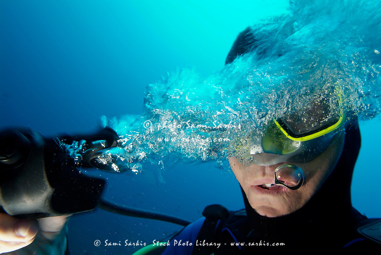 One scuba diver pulls the breathing regulator out of his mouth while still underwater, France.