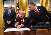 United States President Donald Trump prepares to sign a confirmation for Defense Secretary James Mattis as his Chief of Staff Reince Priebus points to the order while Vice President Mike Pence watches, at the White House in Washington, D.C. on January 20, 2017. <br /> Credit: Kevin Dietsch / Pool via CNP