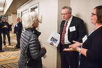 "Sara Altherr, of Kingston, Mass., (center) speaks with Nuclear Regulatory Commission officials (from left) Ray Lorson, Director of NRC Region 1 Division of Reactor Safety and Erin Carfang, Senior Resident Inspector at Pilgrim, after a public hearing regarding Pilgrim Station, a nuclear power plant run by Entergy, at Hotel 1620 in Plymouth, Massachusetts, USA, on Tues., Jan. 31, 2017. Altherr raised concerns about the vulnerability of the plant to attack, including from airplanes from regional airports. An email from the NRC was leaked in December 2016 outlining problems with the ""safety culture"" at the plant and an ""overwhelmed"" staff. Area residents have been calling for the plant to be shut down. The green signs in the audience, reading ""Shut Pilgrim Now,"" are from a group of area residents calling for the plant's closure called Cape Downwinders."