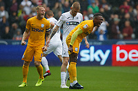 Oli McBurnie of Swansea City (C) looks dejected as Tom Clarke (L) and team mate Darnell Fisher of Preston North End celebrate after he missed scoring from the penalty spot during the Sky Bet Championship match between Swansea City and Preston North End at the Liberty Stadium, Swansea, Wales, UK. Saturday 11 August 2018
