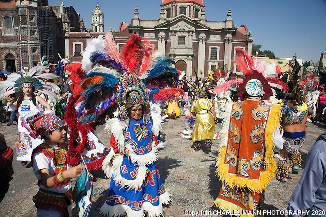 A large troupe of brightly costumed dancers celebrates the Virgin of Guadalupe Feast Day on December 12 in Mexico City in front of the old Basilica de Guadalupe.  Aztec dancers have especially colorful costumes