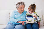 Grandmother and granddaughter (7-8) reading book together