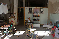 family at home in Havana Vieja, Cuba with pictures of Che Guevara on the wall