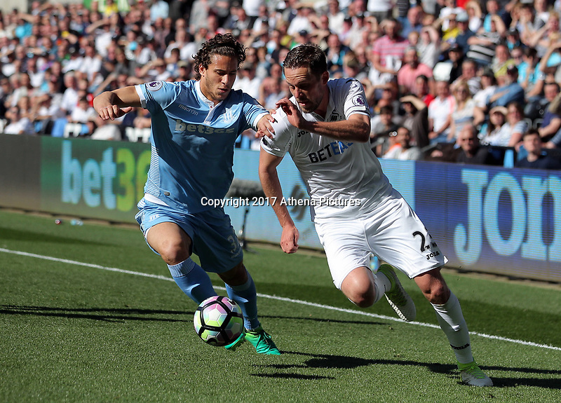 SWANSEA, WALES - APRIL 22: (L-R) Ramadan Sobhi of Stoke City challenges Gylfi Sigurdsson of Swansea City during the Premier League match between Swansea City and Stoke City at The Liberty Stadium on April 22, 2017 in Swansea, Wales. (Photo by Athena Pictures/Getty Images)