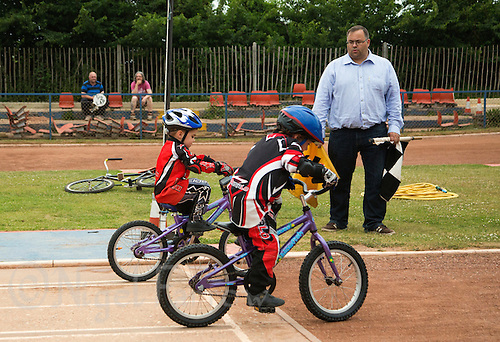 12 JUN 2015 - IPSWICH, GBR - Riders, watched by Ipswich Cycle Speedway Club chairman Jamie Goldsmith, practice starts during an academy training session at Whitton Sports and Community Centre in Ipswich, Suffolk, Great Britain (PHOTO COPYRIGHT © 2015 NIGEL FARROW, ALL RIGHTS RESERVED)