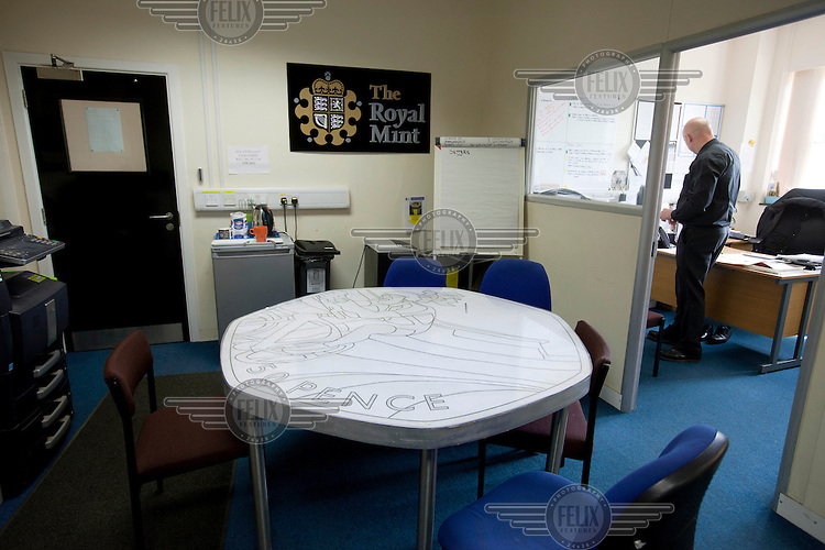 A table, in the offices of the Royal Mint,  near Llantrisant in Mid Glamorgan. It shaped like a British fifty pence coin and decorated with the design of one of the actual coins issued to comemorate the 2012 London Olympic Games. As well as producing coinage for domestic use the mint also manufactures coins for around 60 countries worldwide.