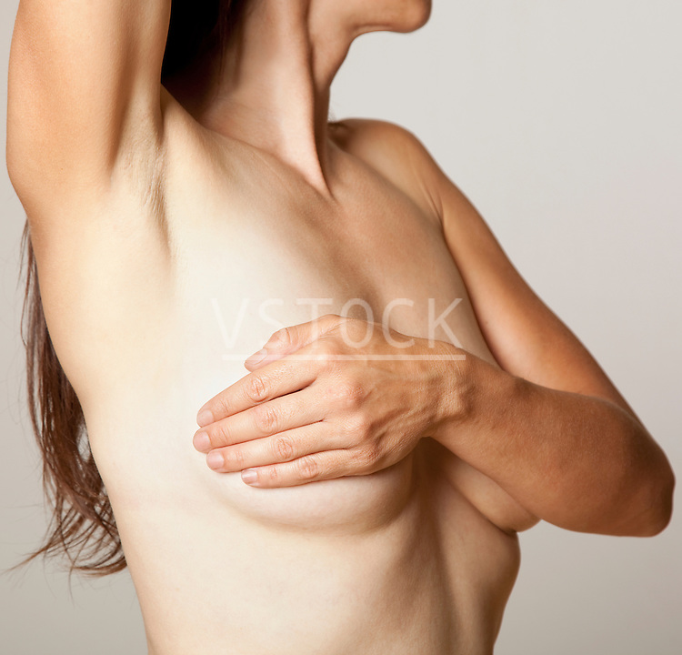 Studio shot of naked woman covering breast, mid section