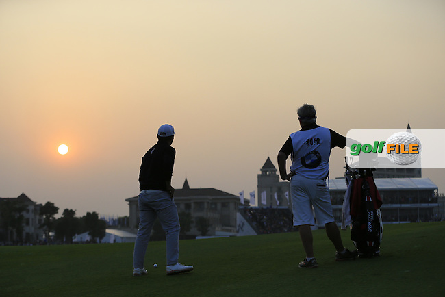 Alexander Levy (FRA) and caddy Bo prepare to play his 2nd shot on the the playoff hole during Sunday's Final Round of the 2014 BMW Masters held at Lake Malaren, Shanghai, China. 2nd November 2014.<br /> Picture: Eoin Clarke www.golffile.ie