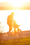 A father teaching his child to ride a bike at sunset.