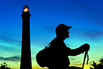 Hiker with backpack and walking stick with Fire Island Lighthouse, Long Island, New York, at dusk on September 20, 2009. Side view of man hiker in silhouette.  (editorial until model release arrives)