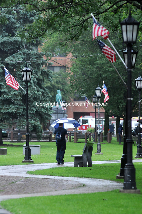 WATERBURY, CT, 13 JUNE 13- 061313AJ01- A man, flanked by American flags hanging from light poles, walks across the Green in Waterbury on Thursday.   Alec Johnson/ Republican-American