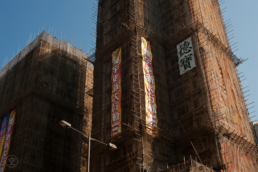 Scaffolding cloaks a multi-story tower building in Hong Kong.
