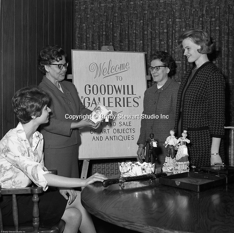 Pittsburgh PA:  Goodwill employees reviewing donated items for inclusion in the Goodwill Galleries Sale.  These items were determined to be more valuable and would generate more money during an antique sale.<br /> In 1966, Goodwill Industries was part of the United Fund Community Chest Agency which eventually became the United Way of Allegheny County in 1974. Goodwill Industries provides a broad array of employment-related education and workforce development programs and services for people with physical and intellectual disabilities and other barriers to employment.