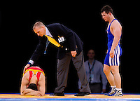 11 DEC 2011 - LONDON, GBR - Beckhan Aldamov (GBR) (in blue) looks on as Batbayer Tserendalai (MGL) (in red) recovers after their men's 66kg category bronze medal bout at the London International Wrestling Invitational and 2012 Olympic Games test event at the ExCel Exhibition Centre in London, Great Britain .(PHOTO (C) NIGEL FARROW)