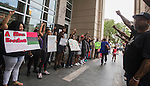 BATON ROUGE, LA -JULY 11: Baton  Rouge citizens walk through protesters staging a silent protest at the East Baton Rouge Parish Courthouse over the Alton Sterling shooting July 11, 2016 in Baton Rouge, Louisiana. Alton Sterling was shot by a police officer in front of the Triple S Food Mart in Baton Rouge on July 5th, leading the Department of Justice to open a civil rights investigation. (Photo by Mark Wallheiser/Getty Images)
