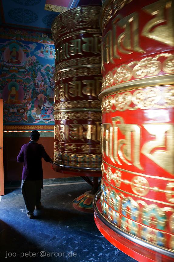 a worshipper circles around the huge prayer wheel below buddhist temple Swayambhu in Kathmandu, Nepal, September 2011