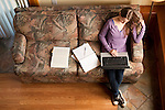 Young college student studying on couch using a computer and taking notes