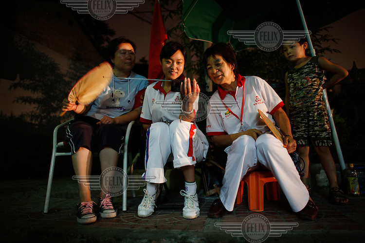 Olympic Games volunteers Li Dong Dong, Guan Li Na and Man Shu Ying watch the closing ceremony on a pocket television in central Beijing.