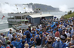 Niagara Falls, Ontario, Canada - 01 August 2006---Tourists / visitors line up for a cruise on the Niagara River, with the Horseshoe Falls (ri), on the Canadian side and the American Falls (le), on the United States' side---nature, landscape, people, transport---Photo: © HorstWagner.eu