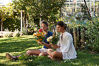 Young women sitting in the garden, arranging fresh flowers