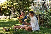 Young women sitting in the garden, arranging fresh flowers