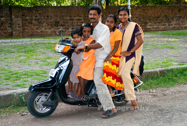 Local Indian family about to go for a ride on their family motor scooter. Cochin, - Kerala, Southern India.