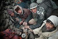 Wakhi men warming themselves around a fire. .Trekking up to the Little Pamir with yak caravan over the frozen Wakhan river.