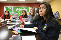 Stefany (cq) Mendoza (right), a freshman at Ozark Catholic Academy, listens to John Rocha, head of school, Tuesday, March 10, 2020, give an introduction to William Shakespeare during Humane Letters class at the school in Tontitown. An anonymous gift of $3 million to Ozark Catholic Academy will reduce tuition by half for kids who graduate from a Catholic elementary/middle school, part of the school's new Continuing Catholic Education program. Check out nwaonline.com/200312Daily/ and nwadg.com/photos for a photo gallery.<br /> (NWA Democrat-Gazette/David Gottschalk)