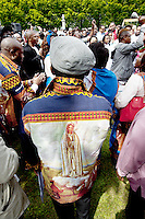 """Switzerland. Canton Valais. St-Maurice. Africa Saints Pilgrimage (Pèlerinage aux Saints d'Afrique). Various religious choirs coming from allover Switzerland sing and celebrate their faith and belief in Jesus  Christ. A man wears a shirt with drawing of """"Our Lady of Fátima """" a title for the Virgin Mary due to her reputed apparitions to three shepherd children at Fátima, Portugal in 1917. The title of Our Lady of the Rosary is also sometimes used to refer to the same apparition. According to religious tradition, Mary was an Israelite Jewish woman and the mother of Jesus. Among her many other names and titles are the Virgin Mary or Blessed Virgin Mary, Mother of God, and Saint Mary in Western churches, Theotokos in Orthodox Christianity, and Maryam, mother of Isa in Islam. The first part of the pilgrimage takes place in Véroliez which is a part of the town of St-Maurice. 2.06.13 © 2013 Didier Ruef"""