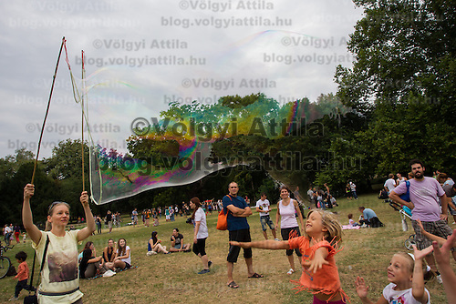 Children burst a giant soap bubble during a soap bubble day in a public park in Budapest, Hungary on August 25, 2013. ATTILA VOLGYI