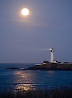 Fine art landscape image of Pigeon Point Lighthouse and full moon, with lighthouse beam shining light over the ocean and full moon reflection on the ocean, along northern California Coast south of Pescadero.