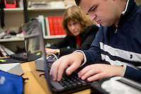 "Logan Kelly, 18, uses a computer and Braille Sense Plus note taker in computer class with Kate Crohan, Teacher of the Visually Impaired in the Secondary Program at Perkins School for the Blind in Watertown, Massachusetts, USA, on Tues., Oct. 15, 2013. Logan was troubleshooting some computer issues and working on the word of the week, ""pilgarlic."" Logan's computer uses screen-reading technology to give an audio picture of what is happening on screen.  The Braille Sense Plus note taker is a word processor that uses standard Brailler input to write in braille and displays the contents of files on a row of changing braille letters on a row close the user."