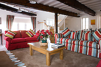 Thee sofas arranged around a wooden coffee table on a large beige rug create an intimate and welcoming seating area in the large living room