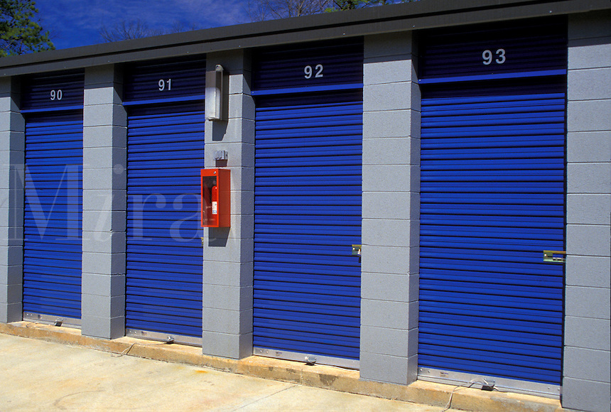 AJ1716, storage units, A red fire extinquisher hangs on the wall next to the blue doors of storage units.
