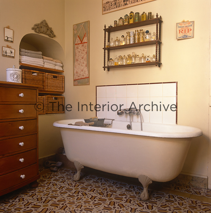 A detail of a yellow bathroom with a tiled floor with a floral pattern. A roll top bathtub with claw feet stands against one wall. Shelves in an alcove and a chest of drawers provides storage. A collection of perfume bottles is displayed on a small wall shelving unit.